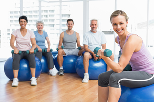Fitness class with dumbbells sitting on exercise ballsの写真素材 [FYI00001788]