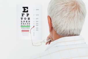 Rear view of a senior man looking at eye chartの写真素材 [FYI00001790]