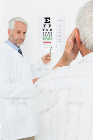 Pediatrician ophthalmologist with senior patient pointing at eye chartの素材 [FYI00001791]