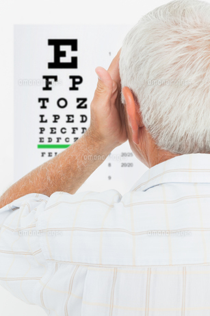 Rear view of a senior man looking at eye chartの写真素材 [FYI00001792]