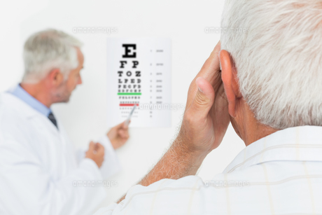 Pediatrician ophthalmologist with senior patient pointing at eye chartの素材 [FYI00001794]
