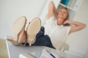 Casual businesswoman sitting at her desk with feet upの写真素材 [FYI00001813]