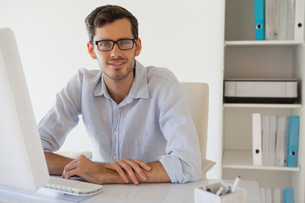 Casual businessman smiling at camera at his deskの写真素材 [FYI00001816]