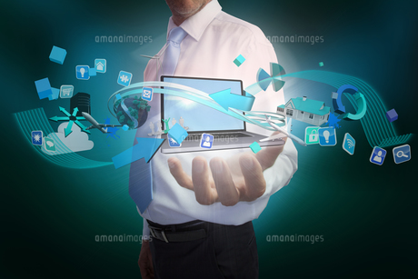 Businessman presenting app icons and laptopの写真素材 [FYI00001817]