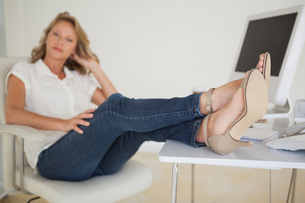 Casual businesswoman sitting at her desk with feet upの写真素材 [FYI00001818]