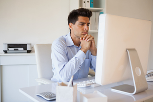 Casual businessman sitting at his deskの写真素材 [FYI00001825]
