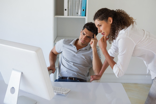Casual business team looking at computer together at deskの写真素材 [FYI00001834]