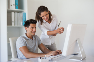 Casual business team looking at computer together at deskの写真素材 [FYI00001835]