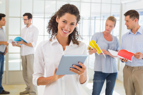 Casual businesswoman using tablet with team behind herの写真素材 [FYI00001838]