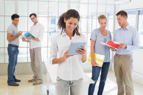 Casual businesswoman using tablet with team behind herの写真素材 [FYI00001843]