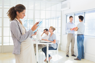 Pregnant businesswoman reading file with team behind herの写真素材 [FYI00001847]