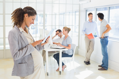 Pregnant businesswoman using tablet with team behind herの写真素材 [FYI00001850]