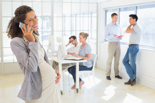 Pregnant businesswoman talking on phone with team behind herの写真素材 [FYI00001851]