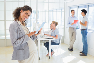 Pregnant businesswoman using tablet with team behind herの写真素材 [FYI00001855]