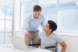 Casual businessman in wheelchair talking with colleague using laptopの写真素材 [FYI00001857]