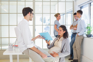 Pregnant businesswoman talking with colleague sitting at deskの写真素材 [FYI00001862]