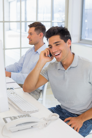 Casual businessman laughing on the phone at his deskの写真素材 [FYI00001866]