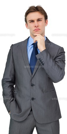 Thinking young businessman in grey suitの写真素材 [FYI00001883]