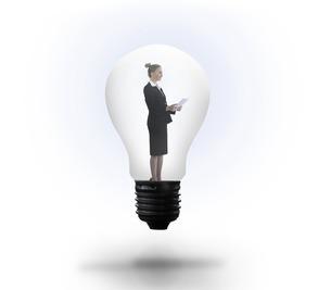 Businesswoman holding tablet in light bulbの写真素材 [FYI00001884]