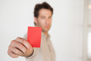 Casual businessman showing red cardの素材 [FYI00001891]