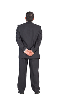 Mature businessman standing with hands behind backの写真素材 [FYI00001895]