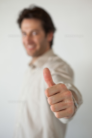 Casual smiling businessman showing thumbs up to cameraの素材 [FYI00001902]