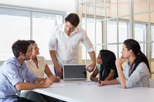 Attractive businessman speaking to coworkersの写真素材 [FYI00001910]