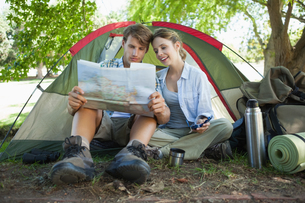 Cute couple sitting by tent reading a mapの写真素材 [FYI00001911]