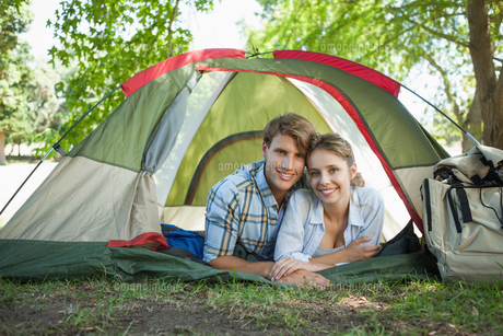 Cute couple lying in their tent smiling at cameraの写真素材 [FYI00001922]