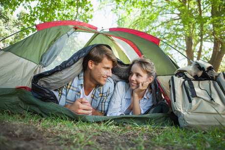 Cute couple lying in their tent smiling at each otherの素材 [FYI00001923]