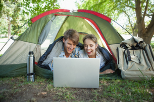 Cute couple lying in their tent using laptopの写真素材 [FYI00001925]