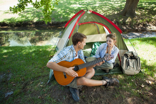 Cute man serenading his girlfriend on camping tripの写真素材 [FYI00001926]