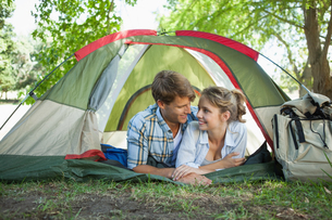 Cute couple lying in their tent smiling at each otherの写真素材 [FYI00001927]