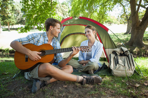 Cute man serenading his girlfriend on camping tripの写真素材 [FYI00001929]