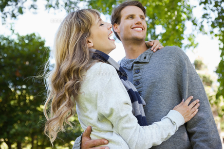 Cute couple embracing and laughing in the parkの写真素材 [FYI00001930]
