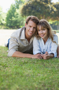 Carefree couple lying in the park smiling at cameraの写真素材 [FYI00001938]