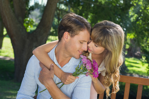Cute couple embracing in the park with girl holding flowersの写真素材 [FYI00001941]