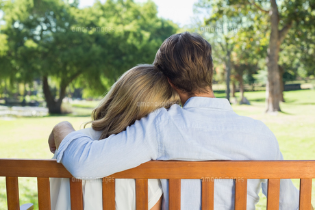 Affectionate couple relaxing on park bench togetherの写真素材 [FYI00001943]