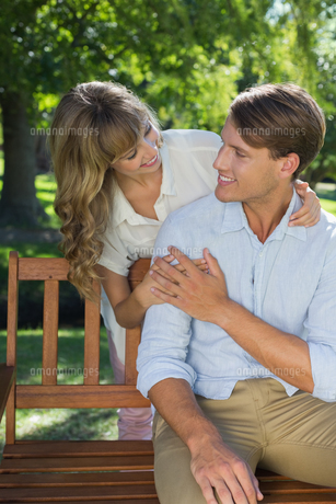Affectionate couple relaxing on park bench togetherの写真素材 [FYI00001947]