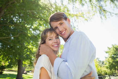Cute couple hugging and smiling at camera in the parkの写真素材 [FYI00001953]