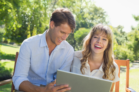 Cute couple sitting on park bench together using laptop and laughingの写真素材 [FYI00001955]