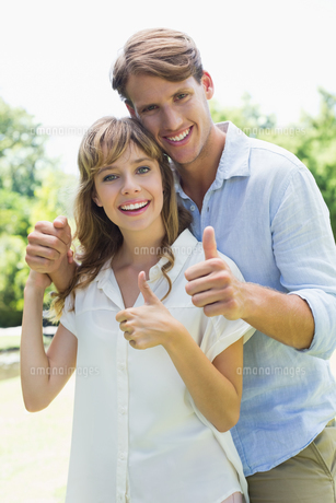 Attractive couple smiling at camera and showing thumbs up in the parkの写真素材 [FYI00001958]