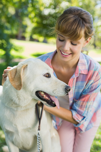 Pretty smiling blonde posing with her labrador in the parkの写真素材 [FYI00001962]