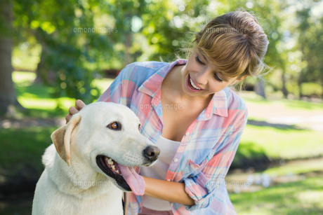 Pretty smiling blonde posing with her labrador in the parkの写真素材 [FYI00001963]