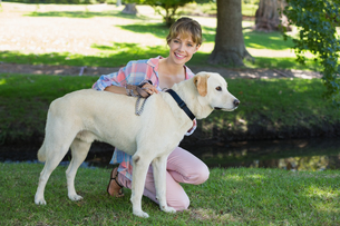 Pretty smiling blonde kneeling with her labrador in the parkの写真素材 [FYI00001967]