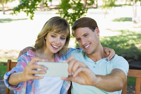 Smiling couple sitting on bench in the park taking a selfieの写真素材 [FYI00001980]