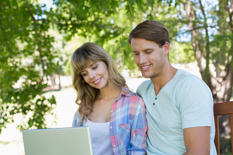 Cute young couple sitting on park bench using laptopの写真素材 [FYI00001985]