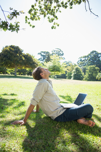Stylish relaxed man using his laptop in the parkの写真素材 [FYI00002001]