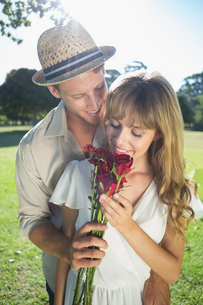 Attractive blonde smeling roses standing with partnerの写真素材 [FYI00002003]