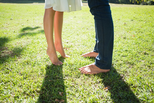 Couples bare feet standing on grassの写真素材 [FYI00002006]